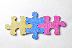 Three colorful puzzle pieces logo