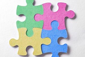 Four colorful puzzle pieces logo