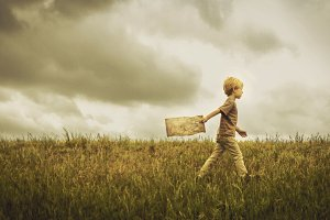 Boy Walking Across Grass with a Map