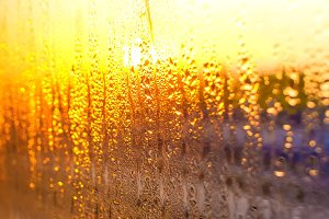 water drops on the glass of the train on the background of the setting sun railroad