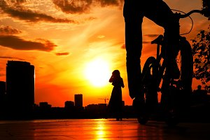cyclist in the foreground against a bright red sunset above city and silhouette of girl