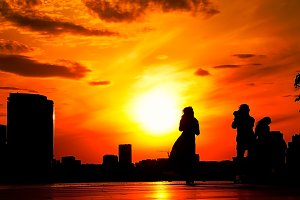 photographer photographs the girl on a background of bright red sunset on the waterfront