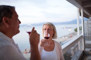 Couple Drinking Red Wine on Balcony