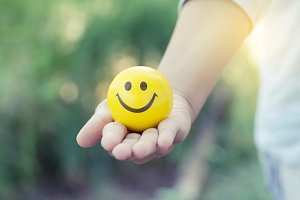Hand holding a smiling yellow ball