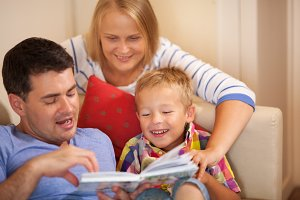 Family reading book together at home