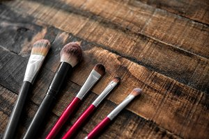 make-up brushes on wooden table
