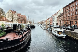 Old city water canal with many baots and old colorful buildings in Copenhagen, Denmark.