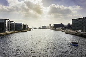 Panoramic view on big water canal with a boat in modern part of Copenhagen, Denmark.