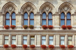 Beautiful medieval castle windows decorated with vivid flower pots