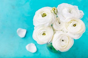 White ranunculus flowers in a ceramic vase