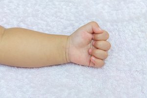 Hand of the baby on white diapers