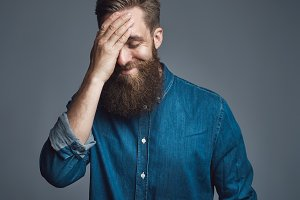 Bearded man in blue denim shirt with hand on head