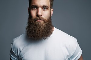 Serious young muscular man with large fuzzy beard