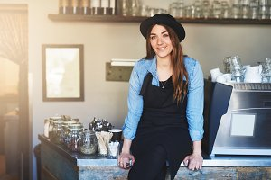 Coffee house owner sits on steel counter