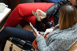Two women using smartphones at cafe in shopping mall.