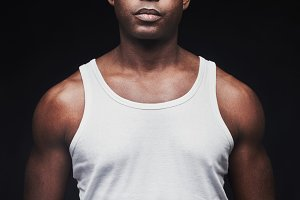 Unemotional young black man in tank top