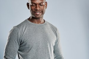 Grinning African man in gray shirt with copy space