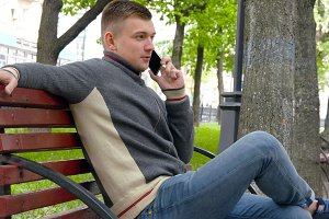 Young man sitting on bench in a city park and talking on the phone