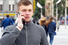 Portrait of a young handsome man talking on cell phone on the city square.