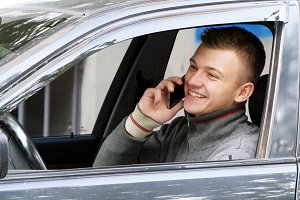 Happy young man pulls over on the road to talk on his cell phone. Businessman in car speaking on the smartphone
