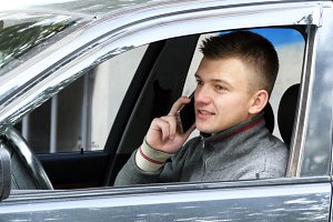 Young man pulls over on the road to talk on his cell phone. Businessman in car speaking on the smartphone