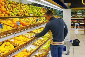 Man with shopping cart choose oranges in the hypermarket