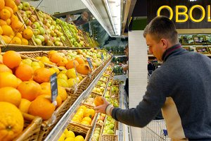 Man choose oranges in hypermarket