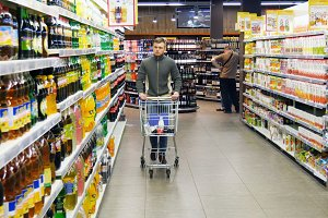 Man with shopping cart walking in the hypermarket