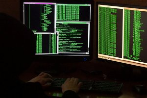 Hacker breaking code. Criminal hacker with black hood