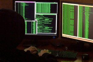 Criminal hacker with black hood penetrating network system from his dark hacker room.