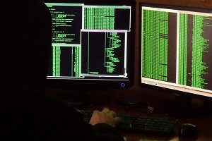 Hacker breaking code. Criminal hacker with black hood penetrating network system from his dark hacker room.