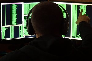 Hacker is looked to binary code. Criminal hacker penetrating network system