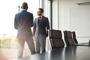 Two businessmen standing talking together