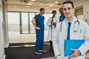 Doctor at hospital standing in front of team