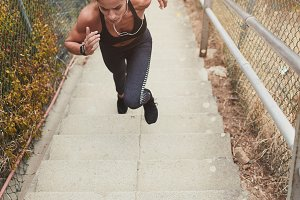 Fit young woman running up stairs