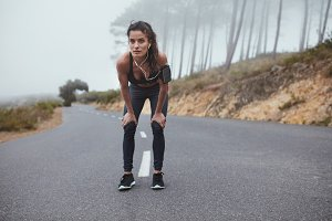 Young woman runner on the road
