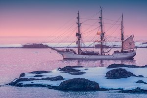 Ship in Antarctica at pink sunset
