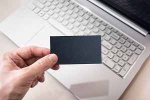 Man Holding Black Business Card