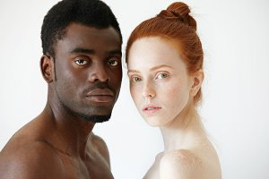 Close up portrait of black man and white woman standing isolated against white studio wall background, looking at the camera. Multi-ethnic love between young African male and redhead Caucasian female