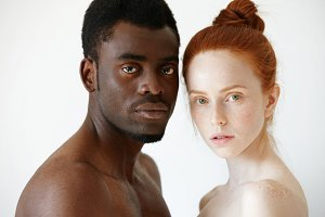 Multicultural love and relationships concept: young nude redhead freckled Caucasian woman standing next to her shirtless African boyfriend, looking at the camera with serious face expression