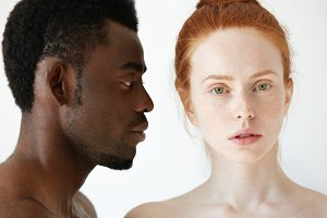 Profile of African male looking at his beautiful Caucasian girlfriend or wife with loving and caring expression on his face, while she is looking at the camera. Interracial multi-ethnic relationships