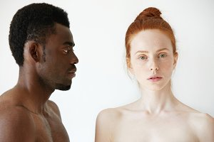 Coffee and milk. Portrait of young multi-ethnic couple posing naked against white studio wall. Profile of African man looking at his Caucasian girlfriend with love and affection. Interracial relations