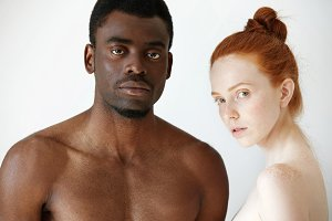 Multi-ethnic love and relationships concept: young redhead Caucasian woman wearing no clothes standing next to her naked African boyfriend, looking at the camera with serious expression on their faces