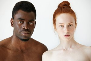 Black and white. Headshot of African man and Caucasian woman standing shirtless and looking at the camera with serious expression. Portrait of young beautiful interracial couple. Mixed race relations