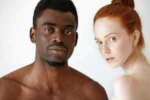 Close up shot of black male and white female posing isolated against white studio wall background. Mixed-race love between young African man and redhead Caucasian woman, looking at the camera