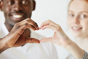 Black and white. Cropped portrait of African man and Caucasian woman looking and smiling at the camera, holding their hands in the shape of heart. Happy interracial couple. Selective focus on hands