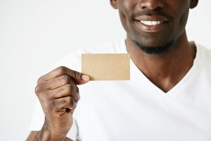 Cropped shot of African male hands holding blank card with copy space for your text or advertising content. Successful smiling businessman wearing white T-shirt showing business card. Film effect