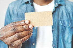 Close up of African man's hands holding business card with copy space for your text or advertising content. Film effect. Black male in white T-shirt and denim jacket showing blank card at the camera