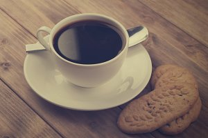 cup of coffee with cookies on old wooden table