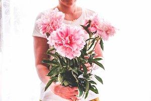 Girl holding pink peonies